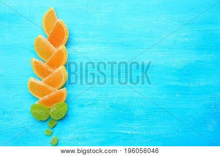 Composition of delicious jelly candies on blue wooden background