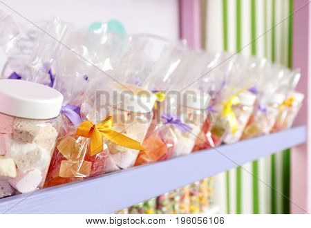 Different sweets on shelf at candy shop