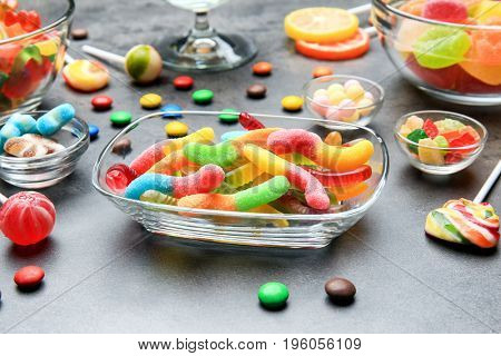 Bowls with delicious candies on grey background