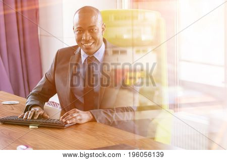 Portrait of smiling young businessman using computer keyboard at desk in office