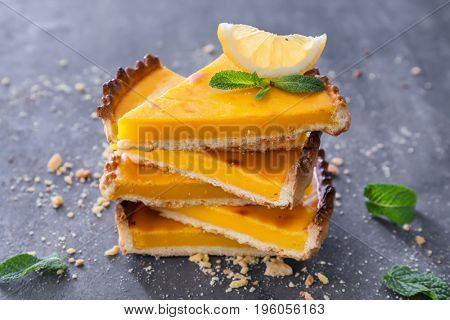 Pieces of delicious lemon pie on textured background