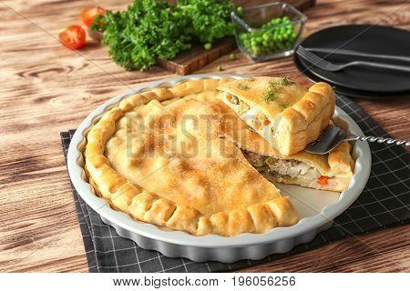 Baking dish with turkey pot pie on wooden background