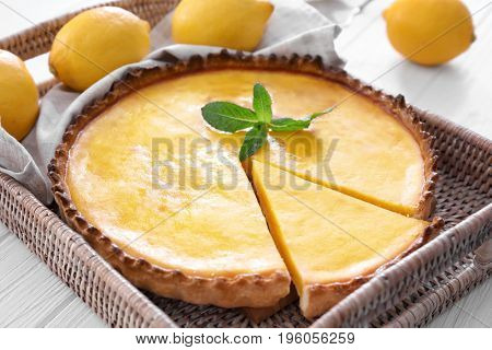 Wicker tray with delicious lemon pie on wooden table, closeup