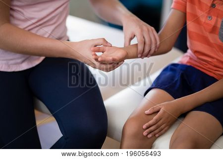 Midsection of female therapist examining wrist with boy sitting on bed at hospital ward