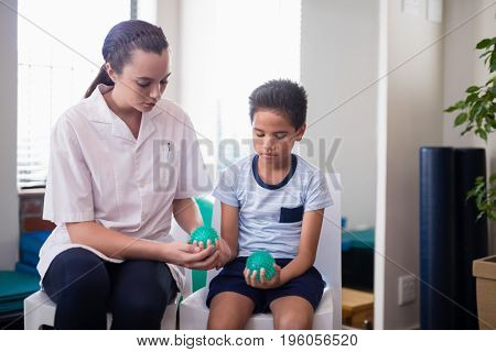 Female therapist sitting by boy on chairs with squeeze balls at hospital ward