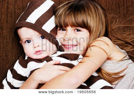 A sister giving her baby brother a hug