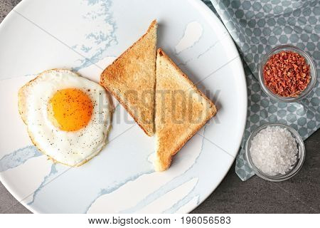 Composition with sunny side up fried egg with toasts and spices on grey table