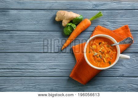 Composition with delicious carrot soup and fresh ginger on wooden table
