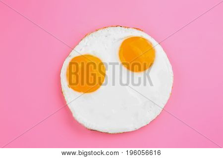 Fried sunny side up eggs  on colour background