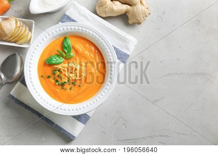 Composition with delicious carrot soup and fresh ginger on table