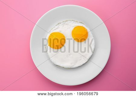 Plate with delicious sunny side up eggs on colour background