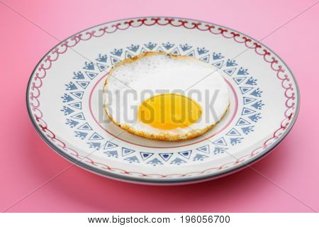 Plate with delicious sunny side up egg on colour background