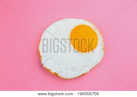 Fried sunny side up egg on colour background