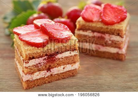 Two pieces of homemade cake with strawberries on wooden table