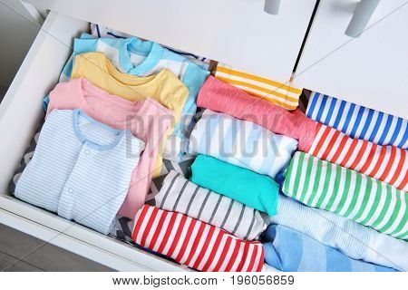 Chest of drawers with clothes in baby room