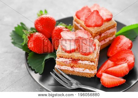 Two pieces of homemade cake with strawberries on plate