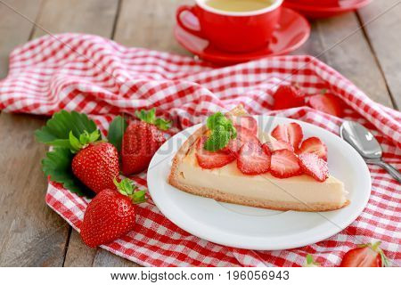 Composition with piece of homemade cake and strawberries on plate
