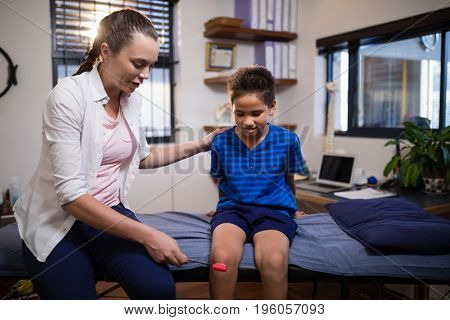 Young female therapist examining boy with reflex hammer on knee while sitting on bed at hospital ward