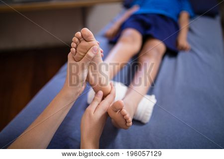 High angle view of boy lying on bed receiving foot massage from female therapist at hospital ward