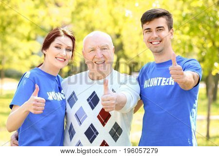 Happy senior man and young volunteers outdoors on sunny day