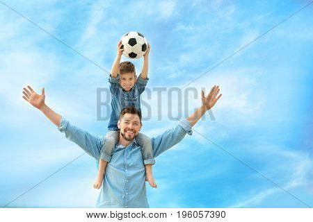 Dad and son with soccer ball outdoors