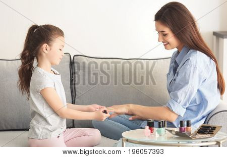 Young woman and her little daughter doing nails at home