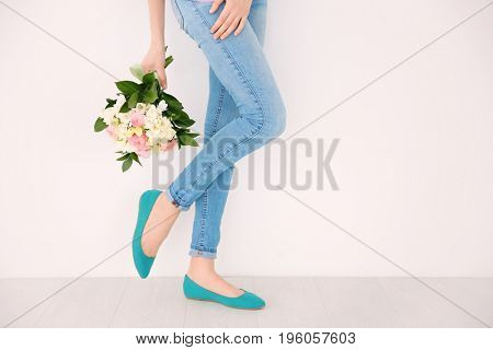 Young woman holding beautiful bouquet with freesia flowers on white background