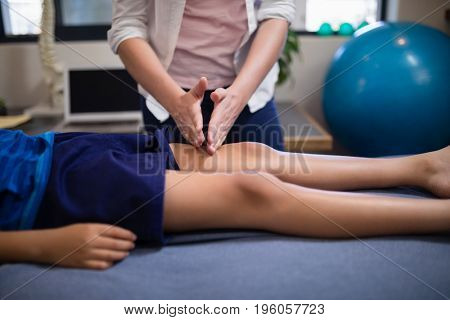 Young female therapist massaging knee of boy lying on bed at hospital ward