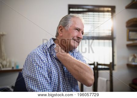 Senior male patient grimacing with neck pain at hospital ward