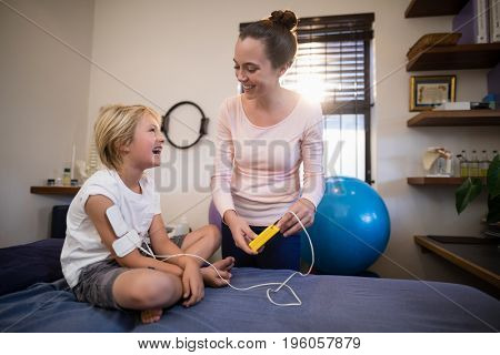 Cheerful female therapist and boy looking at each other with electrical muscle stimulation machine in hospital ward