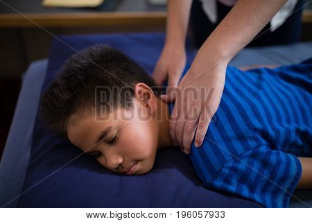 High angle view of boy sleeping on bed while receiving back massage from female therapist at hospital ward