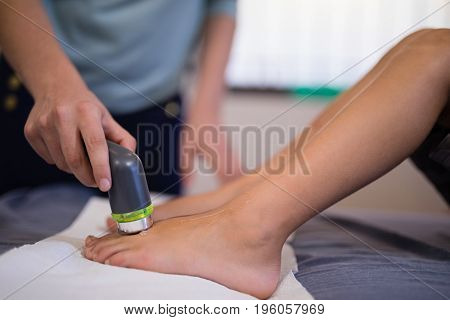 Low section of boy receiving ultrasound scan on feet from female therapist at hospital ward