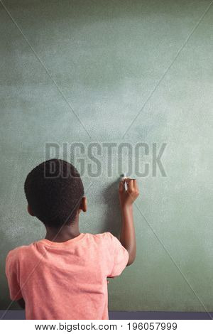 Rear view of boy writing with chalk on greenboard in classroom