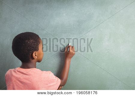 Rear view of boy writing with chalk on greenboard in school