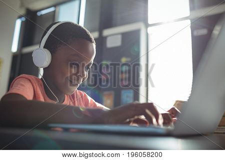 Close up of boy listening music while using laptop at desk in school