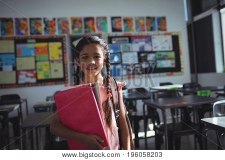 Portrait of girl holding books while standing in classroom