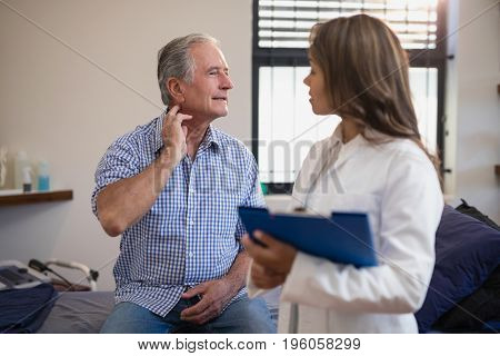 Senior male patient showing neck sprain to female doctor with file at hospital ward