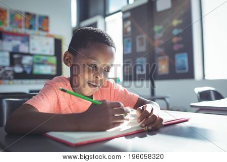Close up of boy writing in book on desk at classroom