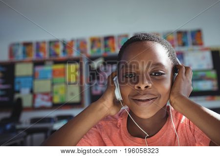 Close up portrait of boy listening music with headphones in classroom