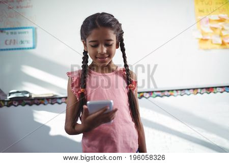 Girl using mobile phone while standing against wall in school