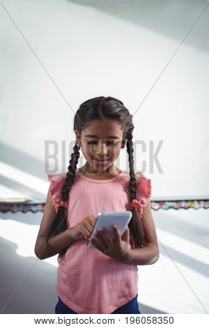 Girl using cellphone while standing against white wall in school