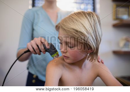 Boy looking at shoulder with female therapist using ultrasound scan in hospital ward