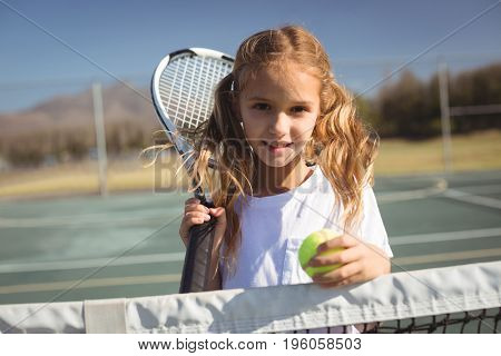 Portrait of girl holding tennis racket and ball while standing by net on court
