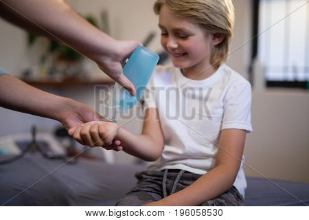 Cropped hands of female therapist pouring scanning gel on wrist at hospital ward