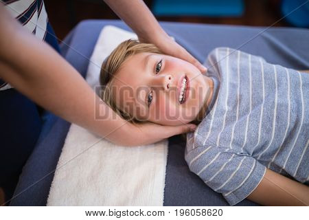 High angle portrait of smiling smiling boy receiving massage from female therapist at hospital ward