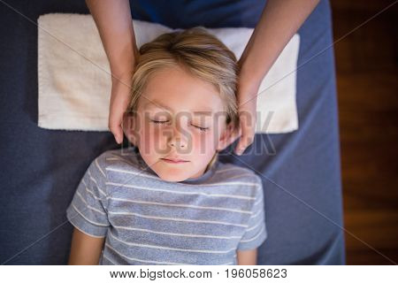 Overhead view of boy with eyes closed receiving neck massage from female therapist at hospital ward