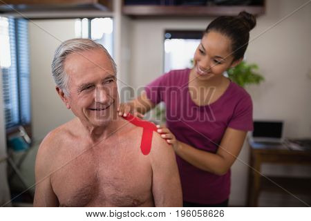 Female therapist applying elastic therapeutic tape on shoulder of smiling shirtless senior male patient at hospital ward