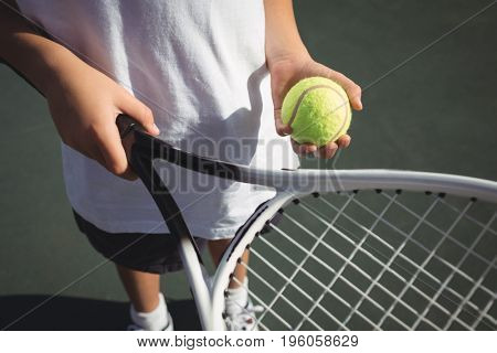 Midsection of girl holding tennis racket and ball while standing on court
