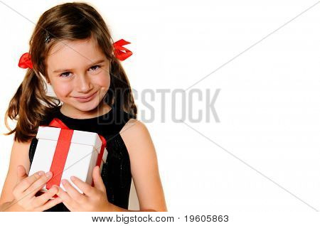 A cute young girl holding a christmas gift, copy space