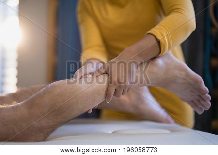 Midsection of female therapist massaging calf of male patient lying on bed at hospital ward